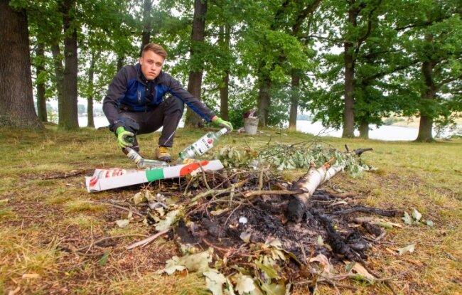 Und hier landet das Holz: Wilde Lagerfeuer sind Gefahr und Ärgernis zugleich. Jonas Walter, stellvertretender Staumeister, mit dem Müll einer Nacht.