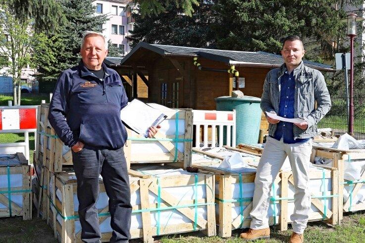 Bauunternehmer Michael Rudolph (l.) und Hauptamtsleiter Robby Safferthal mit Plänen und Baumaterial für das Grüne Klassenzimmer an der Grundschule Fraureuth.