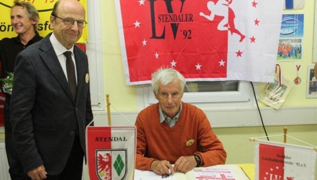 Gunter Fischer trägt sich in das Ehrenbuch der Sport- und Hansestadt Stendal ein. Links neben dem Freiberger steht der Oberbürgermeisters von Stendal, Klaus Schmotz (CDU).