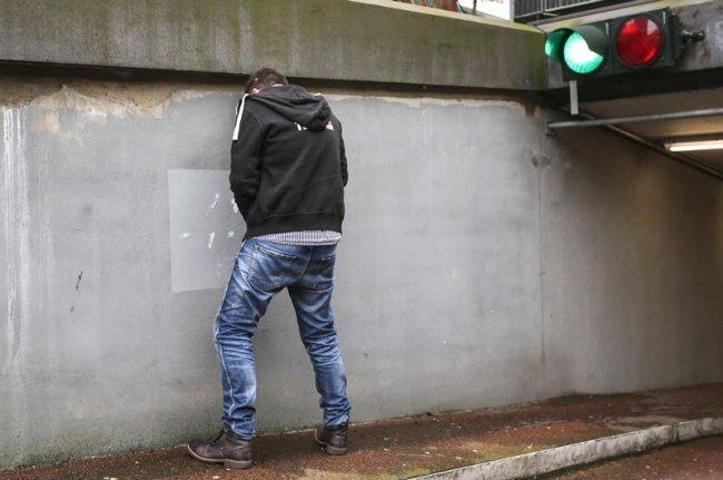 Ein junger Mann simuliert in Hamburg wildes Urinieren. Bad Elster will nun mit Bußgeld gegen sogenannte Wildpinkler vorgehen.