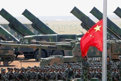 Zur Militärparade zum 90. Geburtstag der Volksbefreiungsarmee auf der Zhurihe Trainings-Basis, 400 Kilometer nordwestlich von Peking, im Jahr 2017 wurde eine Fahne gehisst. Im Hintergrund sind Haubitzen und Raketenwerfer zu sehen.