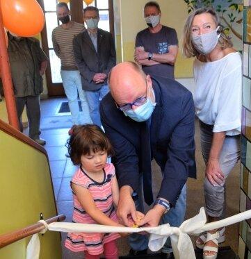 Isabella und Bürgermeister Sandro Bauroth schneiden das Band am Aufgang zu den neuen Räumen durch. Rechts Kitaleiterin Sylvia Pabst.