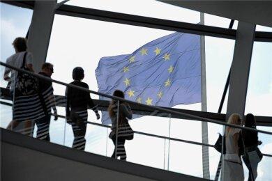 """Eine Europafahne weht über der Kuppel des Reichstags in Berlin. """"Deutschland ist größer als die nächstgrößten Nachbarn, aber nicht groß genug, um ganz Europa zu dominieren."""" Das ist für Herfried Münkler """"das klassische geopolitische Problem Europas""""."""