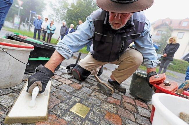 Gunter Demnig verlegt den Stolperstein für Lina Heinrich an der Kohlenstraße 23 in Brand-Erbisdorf. Katrin Dietze (h.r.) von der Initiative für Demokratie Mittelsachsen legte anschließend eine Blume nieder.
