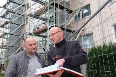Beim Aufzugsanbau an der Julius-Mosen-Straße stimmt sich Marco Strobel (r.), Projektverantwortlicher der Wohnungsbaugenossenschaft Reichenbach, kurz mit René Wollenschläger von der Malerfirma Skotarczak aus Lößnitz ab, die Dämm- und Fassadenarbeiten vornimmt.
