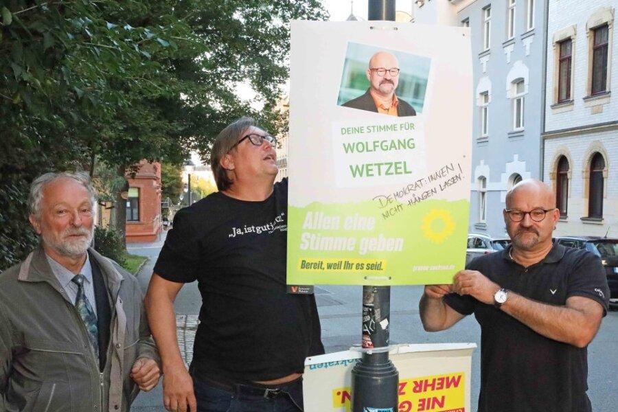 """Um es dem """"Dritten Weg"""" mit ihren """"Hängt die Grünen""""-Plakaten so schwer wie möglich zu machen, wollen die Bündnisgrünen in Zwickau weitere eigene Plakate anbringen. Martin Böttger, Jörg Banitz und Wolfgang Wetzel (von links) fingen am Dienstagabend in der Spiegelstraße damit an."""
