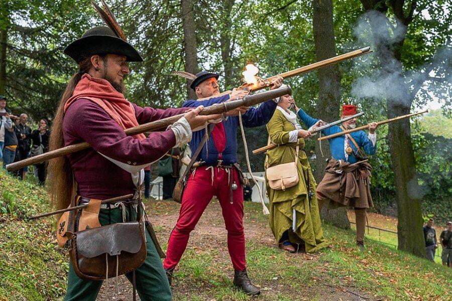 Die Ehrbare Mannschaft des Vogtlandes, (von links) Daniel Klötzer, Rico Ehlert, Sina Klausnitz und Steffen Kretzschmar, lässt auch diesmal Stangenbüchsen und eine Kanone im Burggarten donnern.