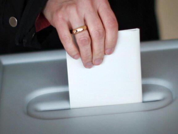 Eine Person wirft in einem Wahllokal den Stimmzettel in eine Wahlurne.