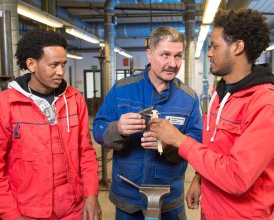 Schweißlehrer Harald Mogel (Mitte) erklärt Awet Afewerki (l.) und Esmael Mahmud, die aus Eritrea nach Dresden geflüchtet sind, das Handwerk.