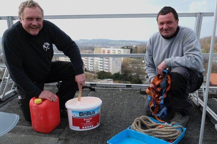 Über den Dächern Reichenbachs. Frank Krause (links) und Holger Gey rückten am Donnerstag dem Graffito an der Dachkante des Hochhauses zu Leibe.
