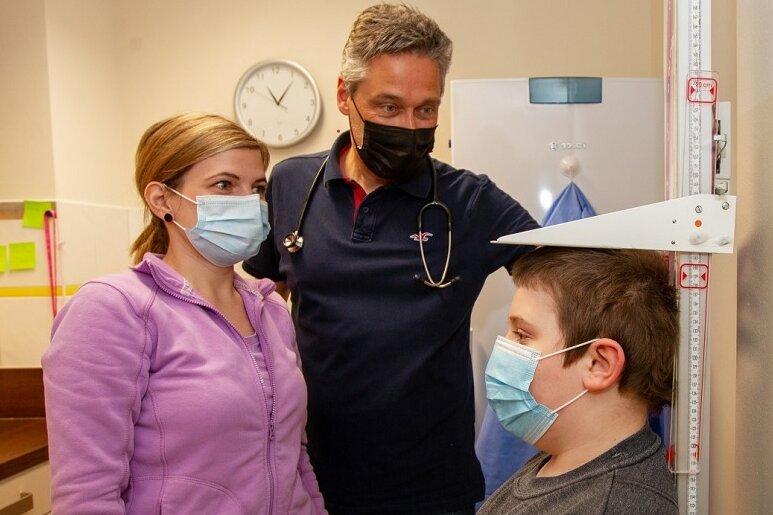 Kinderarzt Dr. Peter Quick und Schwester Stefanie Stolz gemeinsam mit dem neunjährigen Jimmy bei dessen Vorsorgeuntersuchung. Inzwischen spricht der Mediziner Eltern direkt auf diese Termine an.