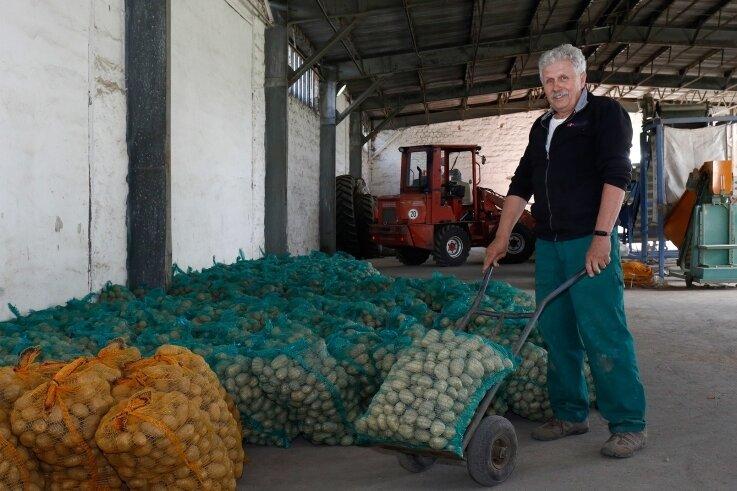 Stefan Jungandreas im Kartoffelverkauf der Agrargenossenschaft Schönberg mit Erdäpfeln in gelben und grünen Netzen.