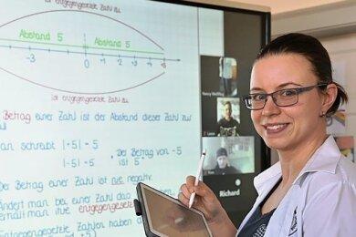 Hier funktioniert es: Nancy Weißflog unterrichtet an der Internationalen Oberschule Niederwürschnitz Mathe und Chemie. Sie kann sich beim Homeschooling auf moderne Unterrichtsmittel stützen, wie diese interaktiven großformatigen Touch-Panels. Was sie auf ihrem iPad notiert, erscheint für alle auf dem Bildschirm. Auf Fragen antworten die Schüler übers Mikrofon oder im Chat. Selbst Gruppenarbeit und Elternsprechstunden sind mit der Technik möglich.