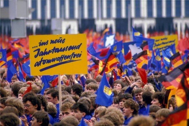 FDJler in Blauhemden und mit blauen Fahnen während einer Demonstration zum 1. Mai 1986 in Ost-Berlin.