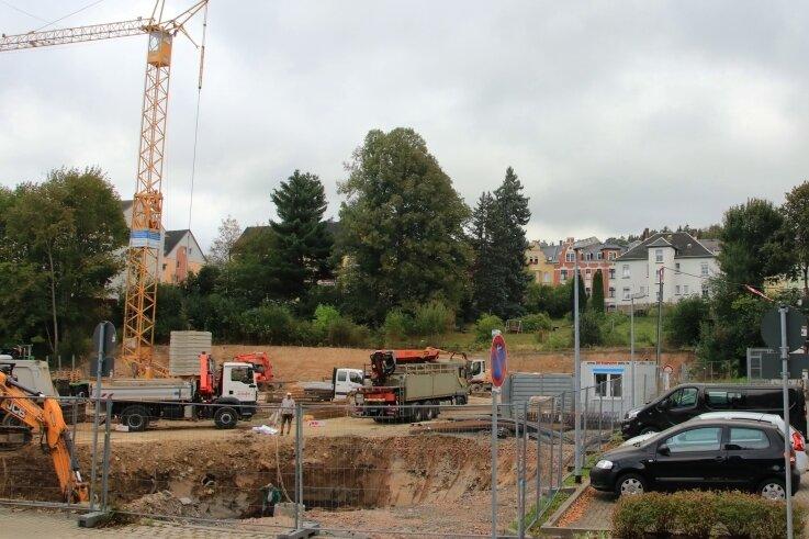 Bagger, Lastwagen und ein Kran zeigen, die Bauarbeiten für den neuen Einkaufsmarkt haben begonnen.