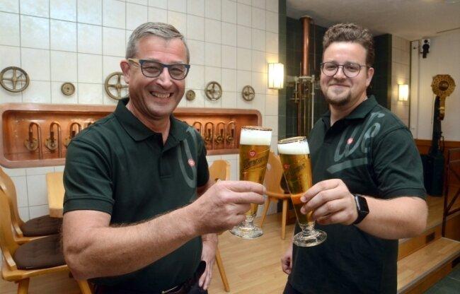 Gunnar und Alexander Ott (von links), die Betreiber der Wernesgrüner Brauschenke auf dem Gutshof, stoßen auf die Wiedereröffnung an.