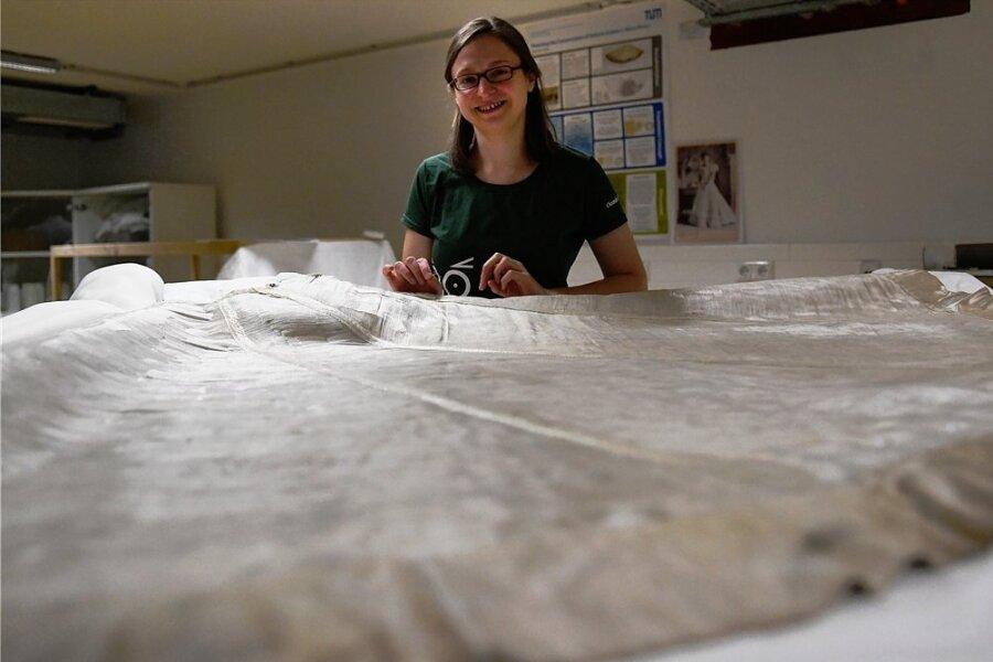 Restauratorin Charlotte Holzer arbeitet an einem Glasfaserkleid, das die Prinzessin Eulalia zur Weltausstellung 1893 trug.