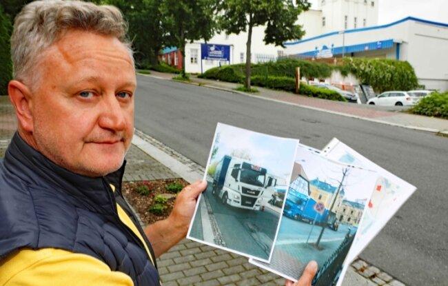 Bodo Steinhauser mit Aufnahmen, die er von den Lieferfahrzeugen gemacht hat. Hinter ihm ist der Rest eines Baumes zu sehen, der von einem Laster umgefahren wurde.