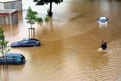 Unwetter und Hochwasser 2002 in Aue. Ein Autobesitzer versucht sein Fahrzeug zu erreichen, bevor es von den Fluten endgüldig geschluckt wird.