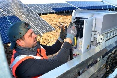Ingo Daniel von der Firma Schoenergie hat am Dienstag im Solarpark in Dittersbach einen Wechselrichter verkabelt.
