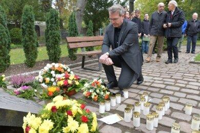 Oberbürgermeister Sven Krüger zündete auf dem Donatsfriedhof eine Kerze an und legte ein Blumengebinde nieder.