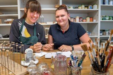 Unter Anleitung von Holzspielzeugmacherin Marie-Theres Langer (r.), die im Betrieb für die Ausbildung zuständig ist,bemalt Maria Hansen Schuhe für die Miniaturfigur Aschenbrödel.