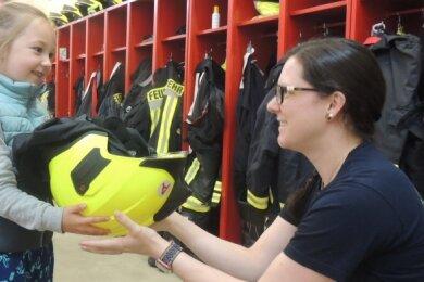 Feuerwehrfrau Karin Werner zeigt Emma Clemens, wie schwer der Schutzhelm ist. Die Gäste aus der Kinderstube Leubnitz waren begeistert.