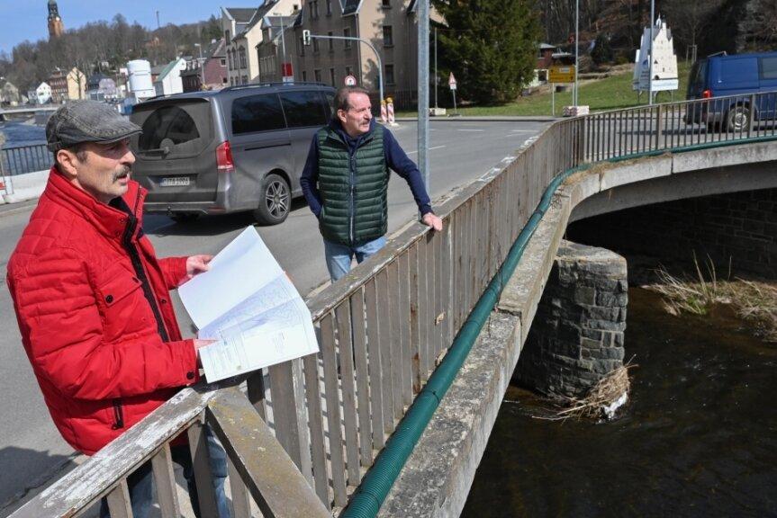 Bauunterlagen und Bauzeit im Blick: Anwohner Ralf Kirchübel (links) und Ralf Clausing auf der Brücke an der Annaberger Straße, die nach Ostern abgerissen und bis 2022 durch einen Neubau ersetzt werden soll.