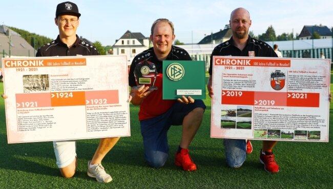 Christoph Meyer, Jens Benedict und Marcel Neubauer (v. l.) vom SV Neudorf freuten sich über einige Geschenke und eine zwölfseitige Chronik auf Tafeln, die in den Vereinsräumen ihren Platz finden werden.