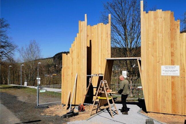 Das erste Portal an der Blockline-Strecke wird derzeit aufgebaut. Holzdesigner Jan Hauffe aus Nassau bekam den Auftrag für die neun Tore, Hans-Jürgen Schulze (im Foto), Holzgestalter aus Frauenstein, arbeitet gemeinsam mit ihm.