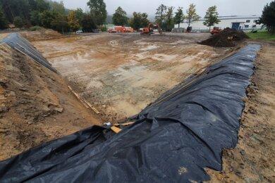 Die etwa 3000 Kubikmeter große Baugrube für die neue Grundschule in Grünhainichen ist ausgehoben und wird an den Seiten durch Planen vor Regen geschützt. Nun soll der Rohbau beginnen.