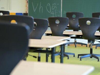 In einem leeren Klassenzimmer sind die Stühle auf die Schulbänke gestellt.