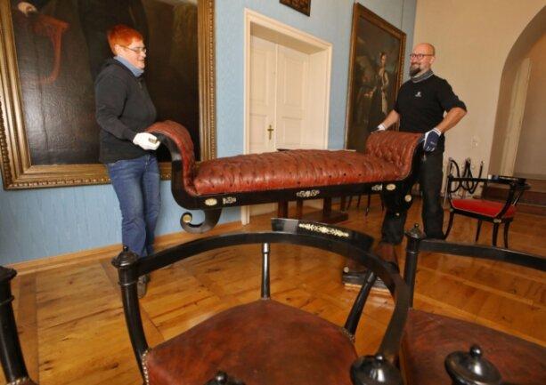 Die Restauratoren Anja Bachmann und Jörg John brachten am Montag die aufwendig restaurierte Récamiere wieder in das Glauchauer Schloss zurück.