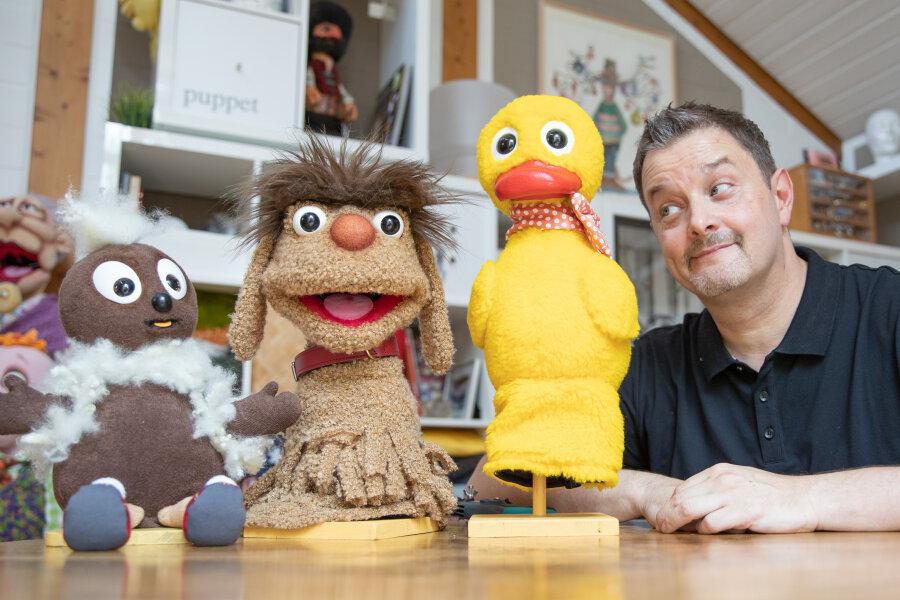 """Der Figurenschneider Norman Schneider neben den Sandmännchen-Puppenfiguren """"Pittiplatsch"""" (l-r), """"Moppi"""" und """"Schnatterinchen""""."""
