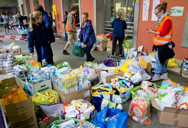Helfer sortieren am Hauptbahnhof in München die Hilfsgüter.