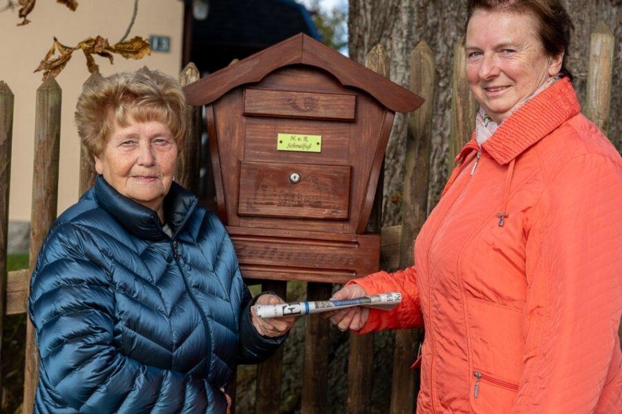 """Noch ein letztes Mal übergibt Regina Müller (rechts) für unser Foto symbolisch die """"Freie Presse"""" an Rosemarie Schmalfuß. Die Zustellerin geht in Ruhestand - im Notfall will sie aber noch einspringen."""