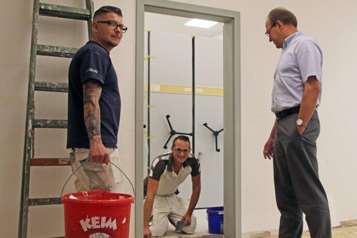 Tobias Jaster (rechts), Leiter des Gebäude- und Flächenmanagements, erkundigt sich bei Marcus Schulze (l.) und Florian Seifert über den Fortschritt der Bauarbeiten im Standesamt.