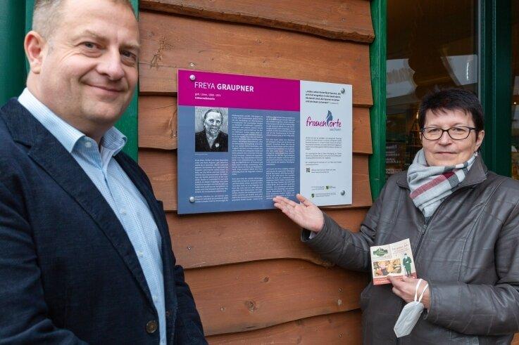 Die Tafel zu Ehren von Freya Graupner hängt am Crottendorfer Räucherkerzenland. Im Bild der Geschäftsführer der Crottendorfer Räucherkerzen GmbH, Mirko Paul, und Andrea Pankau aus den Reihen des Sächsischen Landesfrauenrates.