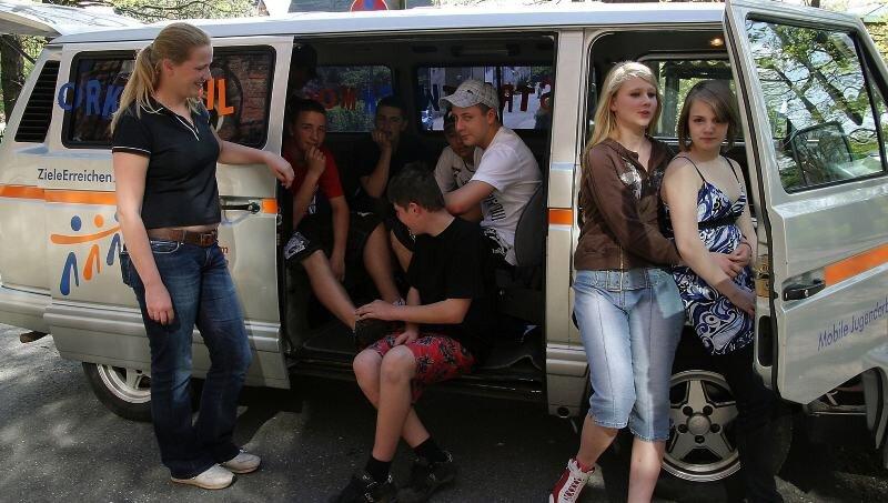 Teresa Junghans (links) ist eine von vier Streetworkern, die mit dem neuen Mobil, wie hier beim Jugendclub in Friedrichsgrün, direkt zu den Treffs der Jugendlichen fahren.