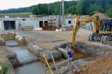 Derzeit wird auch an den Fundamenten der Turnhalle gearbeitet. Einige sind fertig, für andere wird die Erde noch ausgebaggert. Im Hintergrund ist zudem das Gebäude zu sehen, das sich zwischen Halle und Schule befinden wird. Dort sind die Arbeiten schon weiter fortgeschritten.