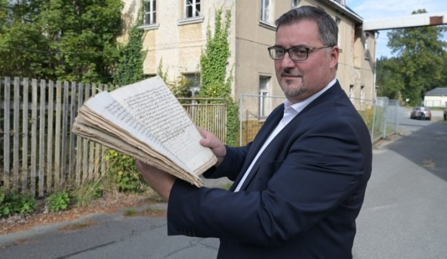 Bürgermeister Volkmar Viehweg mit der Urkunde vor der Alten Mühle, in der das Dokument jahrzehntelang unentdeckt lagerte.