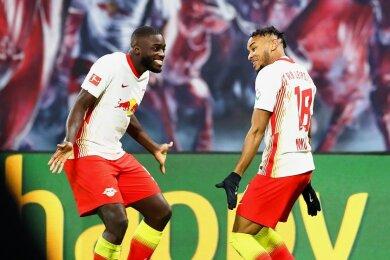 Der Leipziger Dayot Upamecano (l.) bejubelt mit Torschütze Christopher Nkunku den letztlich entscheidenden Treffer zum Sieg gegen Bayer Leverkusen.