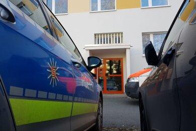 Einsatzkräfte am Eingang zum Wohnhaus an der Straße der Deutschen Einheit.