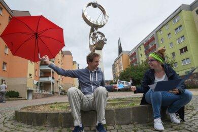 Karola und Robert Köpferl an der Sonnenuhr auf der Sonnenstraße, um die sie eine Blumenuhr pflanzen möchte. Er will über der Straße Regenschirme aufhängen und außerdem Straßenmalerei aufbringen lassen, die dreidimensional wirkt.