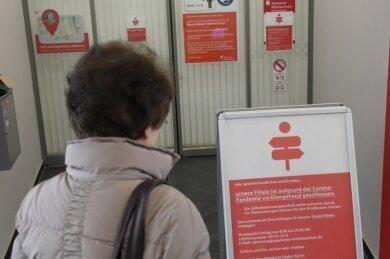 Die seit Wochen zugesperrten Türen zum Servicebereich der Sparkasse in Geringswalde ärgern nicht nur diese Kundin. Ein Aufsteller rät zu Online-Banking und verweist auf Filialen in Rochlitz und Mittweida.