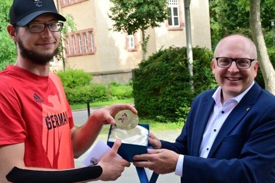 Eine Medaille mit Kulturhauptstadt-Logo als Glücksbringer: Oliver Hörauf (links) wird von OB Sven Schulze verabschiedet.