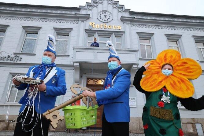 Karsten Zeller, Sven Thumstädter und Nicole Köhler (von links) gaben am Aschermittwoch den Rathausschlüssel zurück. Bürgermeister Sandro Bauroth (FDP) zog den Korb mit einem Seil coronakonform auf den Balkon des Rathauses.