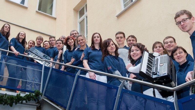 Das aktuelle Gruppenbild entstand im Glauchauer Ratshof-Atrium. Daniel Türschmann (6. von rechts) und Nadin Flechsig (10. von rechts) freuen sich mit den übrigen Mitgliedern von Tacctart auf das Jubiläumskonzert.
