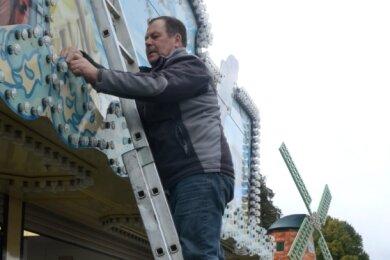 """Hilfe in schwierigen Zeiten: Während Udo Klemm an seinem """"Fischhaus"""" die Beleuchtung wechselt, hält Udo Weichsel die Leiter. Im Hintergrund ist die Mühle von Petra Hasselbart aus Leipzig zu sehen."""