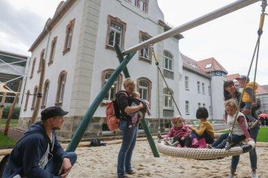 """Kinder mit ihren Eltern auf dem Spielplatz des neuen """"Naturkinderhauses Esche"""", das in den sanierten Gebäuden der Eugen-Esche-Stiftung an der Forststraße entstanden ist. Sie nahmen an der feierlichen Schlüsselübergabe durch die Baufirma Fasa an den Trägerverein KJF am Montagnachmittag teil."""